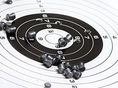 Air gun pellets scattered on a black and white paper target