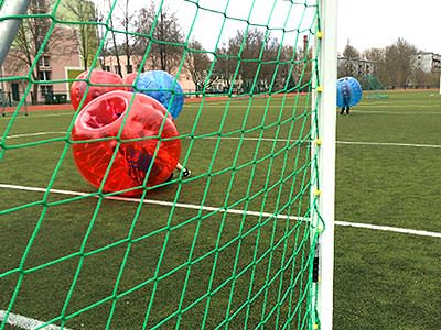 People in red and blue zorbs on a football pitch