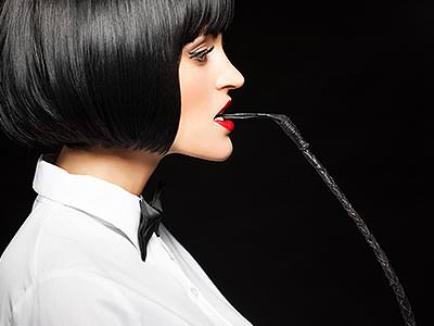 A woman wearing a black wig and a white shirt, holding a whip in her mouth