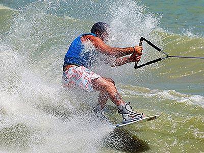 A man wake boarding across green water