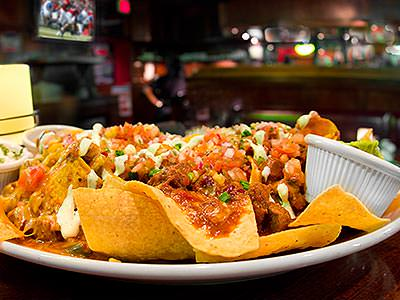A plate of nachos with a sports bar in the background