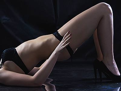 A woman lying on the floor in black underwear, pushing herself up off the ground