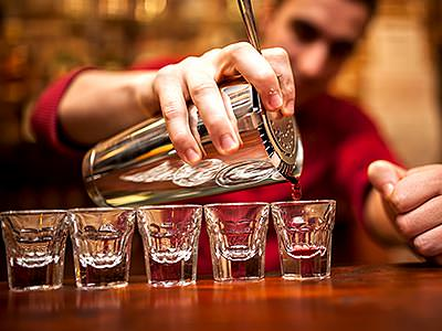 A man filling a row of shot glasses from a metal cocktail shaker