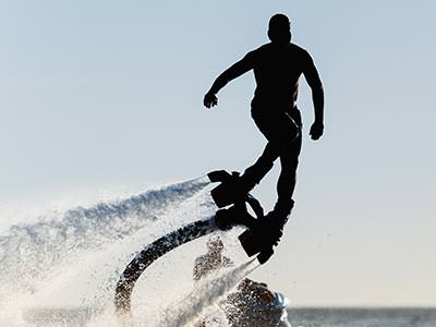 A man on a fly board, flying above the ocean