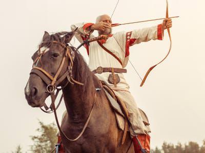 A man in traditional clothing aiming a borrow and arrow whilst sitting on the back of a horse