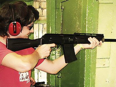 A man wearing ear protection and aiming with a rifle in an indoor shooting range