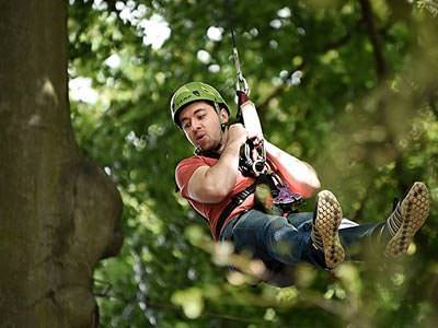 A man wearing a helmet hanging from a rope attached to a harness