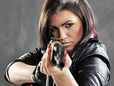 A woman aiming a Kalashnikov-style rifle at the camera