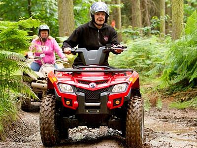 A man driving a quad bike on a muddy path