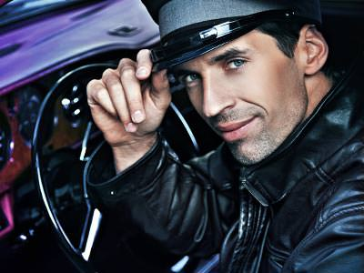 A man in the driver's seat of a car, looking at the camera and tipping his hat