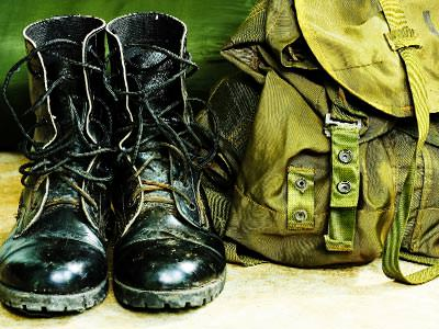 Pair of black army boots next to a green rucksack
