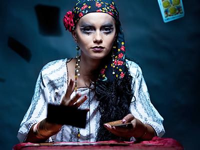 A woman in a fortune teller's outfit throwing playing cards towards the camera