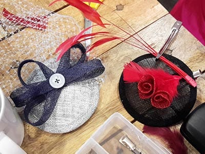 A white fascinator with a black bow and white button with white mesh material attached to it and a black fascinator with two bits of red material rolled to look like roses and red feathers