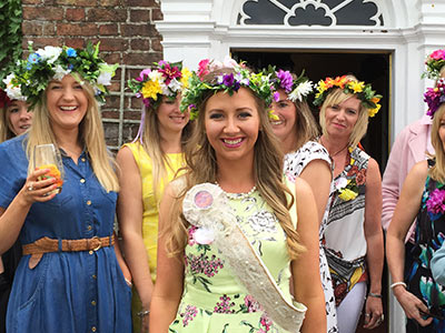 A woman wearing a large fascinator made out of flowers and smiling