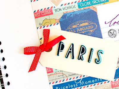A white tag with a red ribbon and the word Paris on, on top of a blue scrapbook