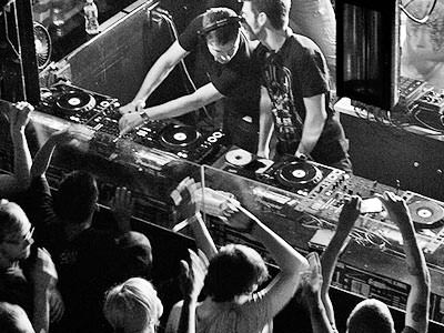Black and white image of to DJs in a booth, performing to a crowd