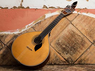A Portuguese guitar balanced against a wall