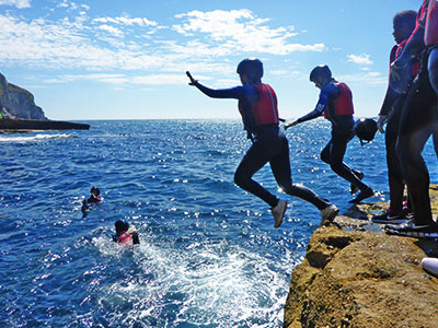 Two people jumping into water off a rock, with a group of people watching