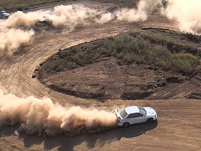 A white car driving around a hairpin bend on a dirt road, kicking up dust behind it