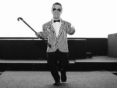 Black and white image of a man with dwarfism wearing a striped jacket and bow tie, and holding a cane