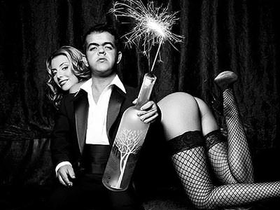 Black and white image of a man with dwarfism holding a large bottle of vodka containing a lit sparkler, in front of a woman posing seductively in lingerie