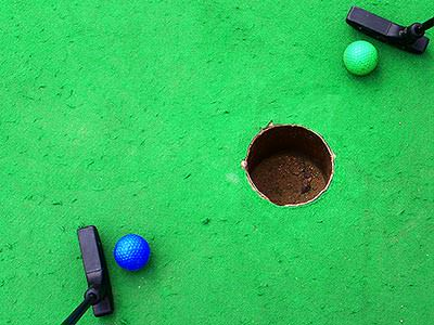 Two golf balls near a hole