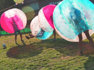 People playing in pink and blue inflatable zorbs, playing on an outdoor pitch