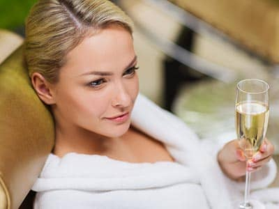A woman wearing a white robe and holding a glass of champagne
