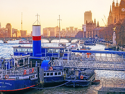 The Tattershall Castle boat moored on the Thames with London landmarks in the background