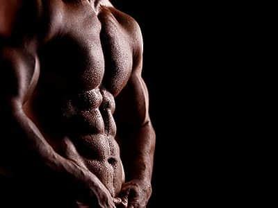A naked male torso to a black backdrop