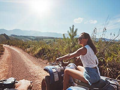 A girl on a quad bike in the sun
