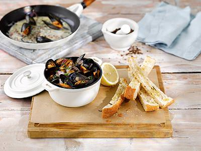 A board with a bowl of mussels and some breadsticks on