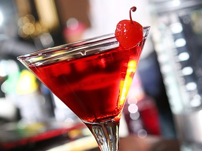 A red cocktail in a martini glass with a cherry on the side