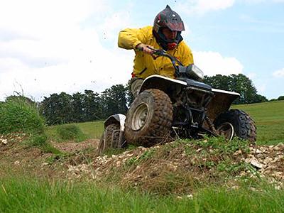Man driving a quad bike over rough terrain