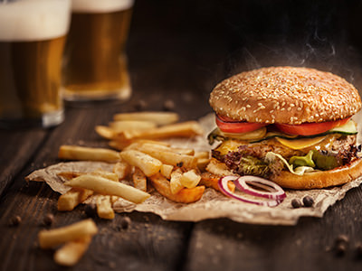 A burger and chips splayed out on a wooden table top with two pints of beer in the background