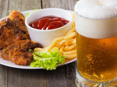 A glass of beer on a wooden table, with some food in the background