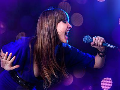 A woman in a blue top singing into a microphone, with a purple background