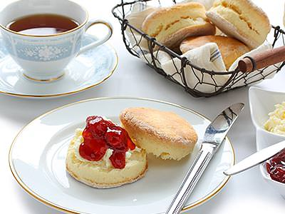A wire tray of scones, a cup of tea and a plate with a jam and cream covered scone on