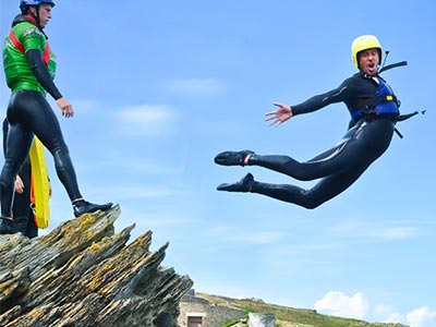 A close up of a man jumping off a cliff as a man looks on