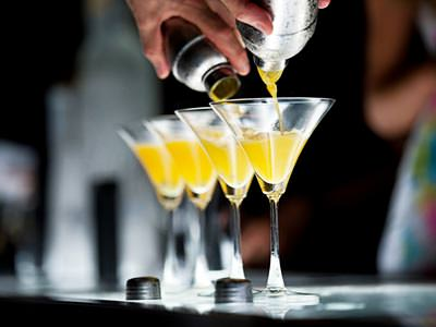A row of martini glasses being filled from a pair of metal cocktail shakers