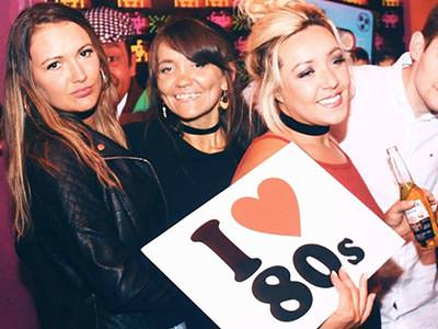 A group of women posing an holding a sign reading 'I LOVE 80s'