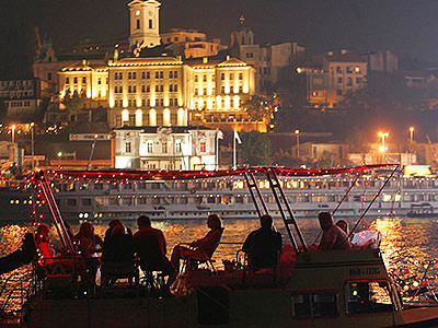 People sat on the top deck of a boat, with buildings lit up in the background, at night