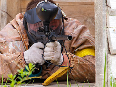 A man in a mask and overalls, lying down and aiming with a paintball gun