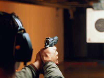 A back shot of a man firing a pistol at a target