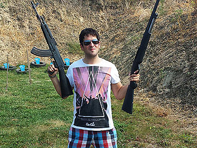 A man holding two guns into the air