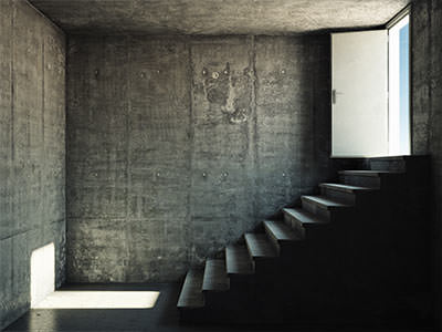 An open white door leading down the stairs to a grey cellar like room
