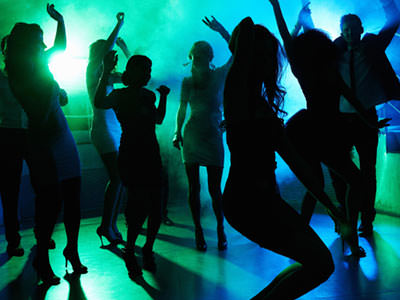 Silhouettes of men and women dancing to a backdrop of green and blue light