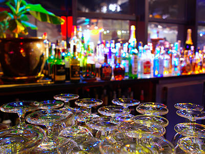 Glasses in the foreground, with spirits on shelves on top of a bar in the background