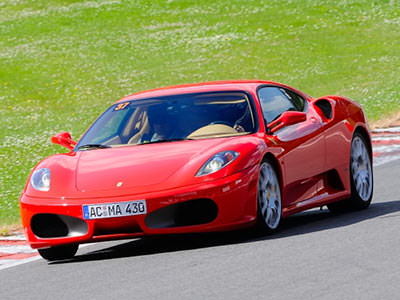 A red ferrari driving on a track