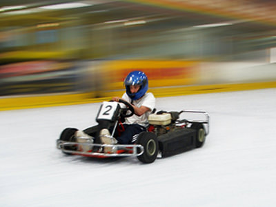 A man in a kart with a number two on the front, driving on ice